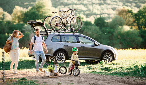 Obraz Family with two small children going on cycling trip in countryside. - fototapety do salonu