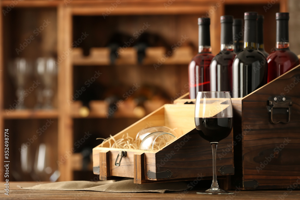 Fototapeta Box with bottles of wine on table in cellar