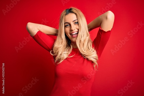 Foto Young beautiful blonde woman wearing casual t-shirt standing over isolated red b