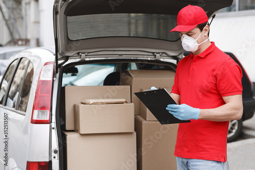 Obraz Transportation of parcels. Courier in protective mask and gloves checks parcel in tablet - fototapety do salonu