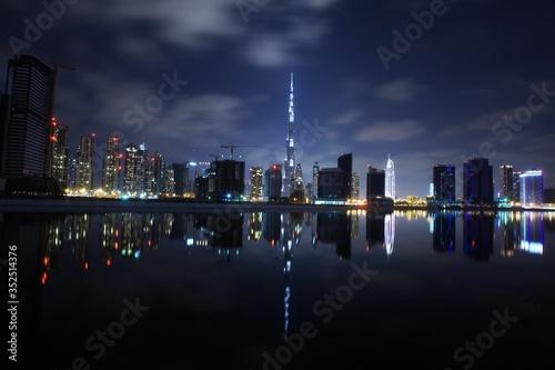 Burj Khalifa By Lake In Illuminated City At Night Fotobehang