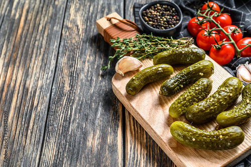 Fototapeta Marinated cucumbers gherkins on wooden cutting board. Pickles with mustard and garlic. Black background. Top view. Copy space obraz