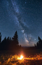 Tourist Camping Near Forest In Dark Warm Summer Night. Bright Campfire Burning Under Beautiful Magical Night Sky Full Of Stars And Shiny Milky Way. Concept Of Camping, Tourism.