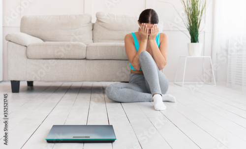 Fototapeta Girl Crying Sitting Near Scales Gaining Excess Weight At Home obraz