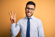 Young Handsome Businessman Wearing Tie And Glasses Standing Over Yellow Background Showing And Pointing Up With Fingers Number Three While Smiling Confident And Happy.