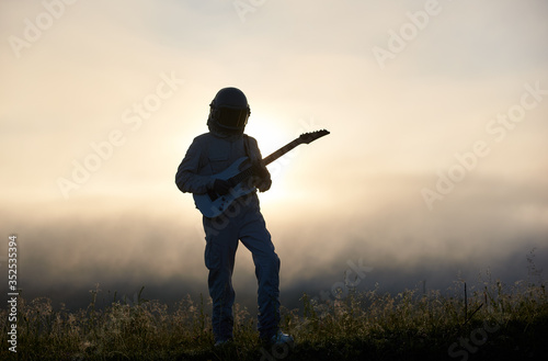 Silhouette of space traveler playing melody on guitar in misty grassy valley with white mystical sky on background Canvas Print