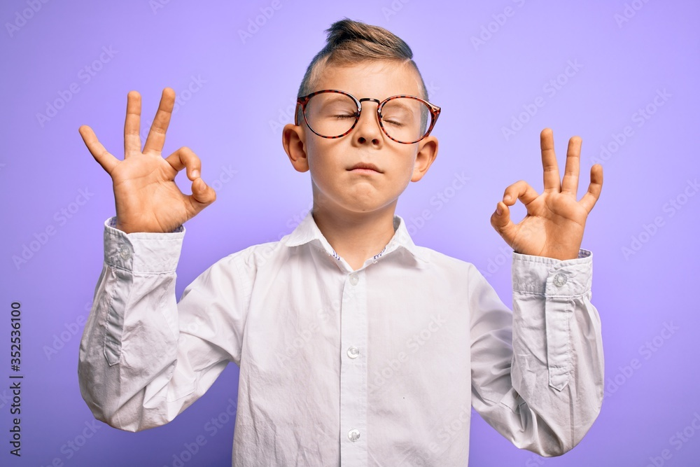 Fototapeta Young little caucasian kid with blue eyes wearing glasses and white shirt over purple background relax and smiling with eyes closed doing meditation gesture with fingers. Yoga concept.