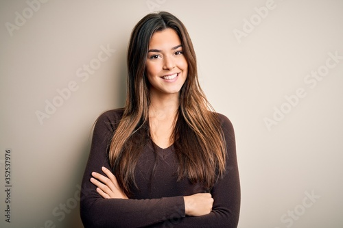 Obraz Young beautiful girl wearing casual sweater standing over isolated white background happy face smiling with crossed arms looking at the camera. Positive person. - fototapety do salonu