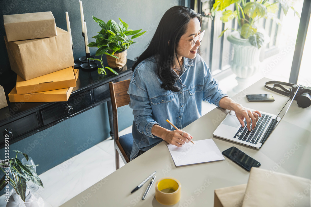 Fototapeta Young business woman working online e-commerce shopping at her shop. Young woman seller prepare parcel box of product for deliver to customer. Online selling, e-commerce.