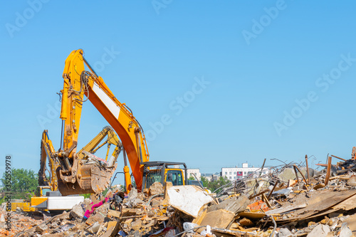 Destruction of old building. Yellow excavator on ruins. Canvas Print