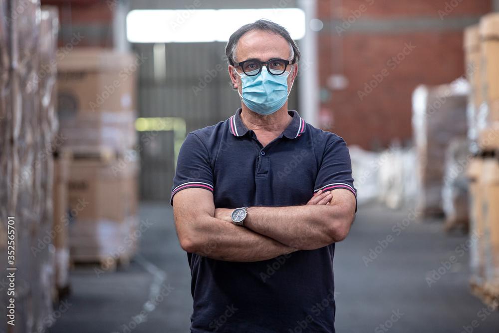 Fototapeta Uomo con occhiali neri e mascherina protettiva incrocia le braccia nel magazzino in cui lavora