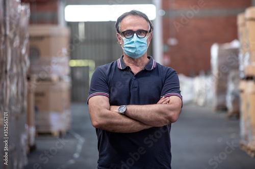 Fényképezés Uomo con occhiali neri e mascherina protettiva incrocia le braccia nel magazzino