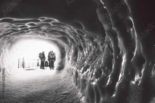 Canvastavla People With Backpacks Standing At Entrance Seen Through Ice Cave