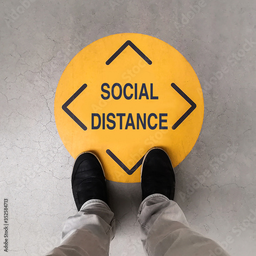 Fototapeta A person standing on a social distancing sign obraz