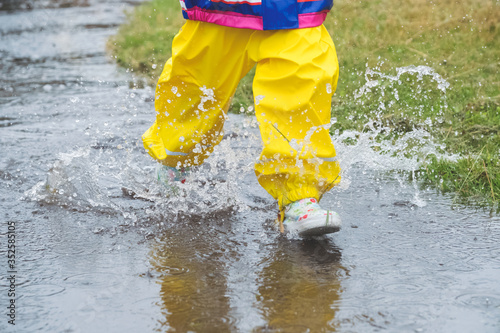Fotografie, Obraz Low Section Of Girl Running Through Puddle