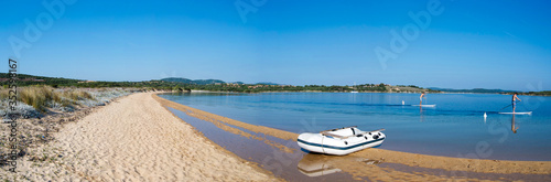 Obraz Inflatable Boat Moored On Lakeshore Against Clear Blue Sky - fototapety do salonu