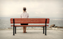 A Lonely Woman Sits On A Bench By The Water. Toned Image.