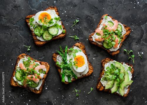 Fototapeta Variety sandwiches with cream cheese, egg, asparagus, avocado, cucumber, shrimp, micro greens on a dark background, top view obraz