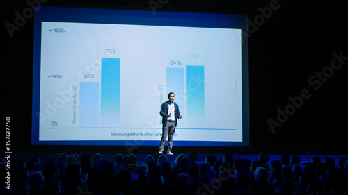 Obraz Startup Conference Stage: Speaker Presents New Product, Talks about Performance, Neural Networks, Artificial Intelligence, Big Data and Machine Learning. Live Event with Large Audience - fototapety do salonu