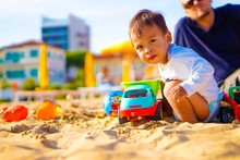 Portrait Of Baby Boy Playing With Toys At Beach While Father In Background