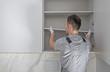 Leinwandbild Motiv Men Installing Modern Bathroom White Cabinets