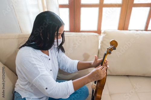 Photo Portrait of a musician at home adjusting the violin