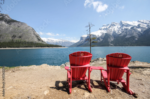Valokuva Empty Red Adirondack Chairs At Lakeshore Against Snowcapped Mountains