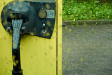 Yellow Vacuum Cleaner, In Parking Lot, With A Euro Coin Slot, Photographed Through Rain Window Pane, Depth Of Field, Germany.