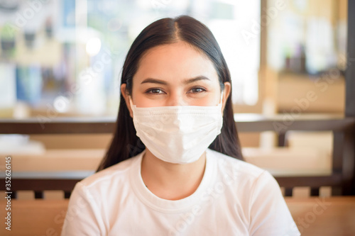 Obraz Woman is eating in Restaurant with social distancing protocol while lockdown City due to  Coronavirus pandemic - fototapety do salonu
