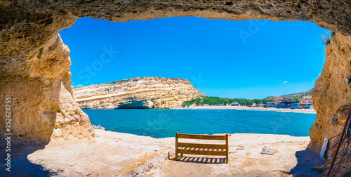 Fotografie, Tablou Matala beach with caves on the rocks that were used as a roman cemetery and at t