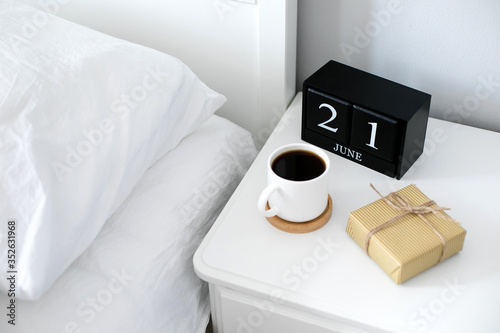 Obraz Morning cup of coffee, gift present, black wooden calendar on bedside table on Happy Fathers Day. Holiday concept - fototapety do salonu
