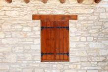 Closed, Dark Wooden Shutters On A Light Sandstone Wall