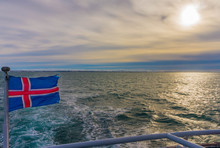Flag Of Iceland On Boat In Sea Against Cloudy Sky