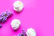 Leinwandbild Motiv Tasty fresh meringue and blooming lilac on bright pink background, top view, copy space for the text