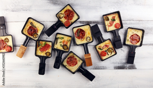 Fototapeta Delicious traditional Swiss melted raclette cheese on diced boiled or baked potato. obraz