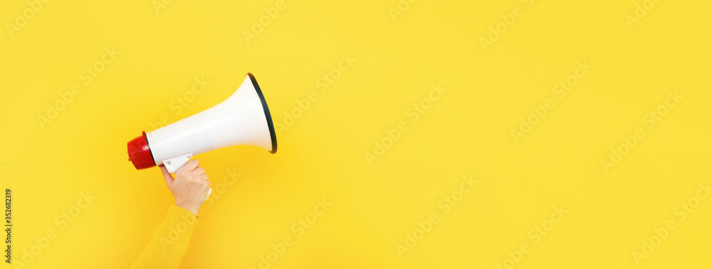 Fototapeta megaphone in hand on a yellow background, attention concept announcement, panoramic mock-up