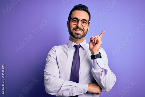 Handsome businessman with beard wearing casual tie and glasses over purple background with a big smile on face, pointing with hand and finger to the side looking at the camera.