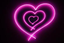 Abstract Illuminated Florescent Three Pink Neon Hearts Sign Light On Black