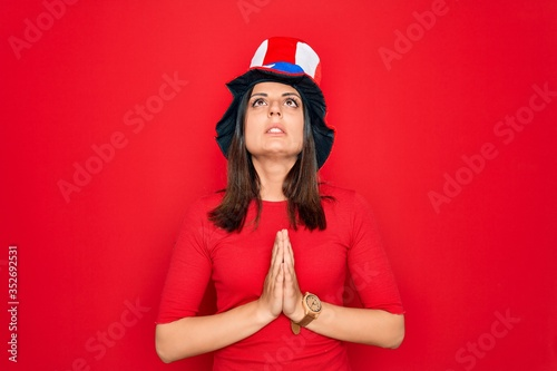 Young beautiful brunette woman wearing united states hat celebrating independence day begging and praying with hands together with hope expression on face very emotional and worried Canvas Print
