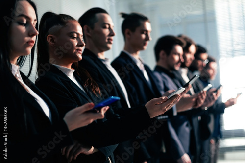 young business people with smartphones standing in line