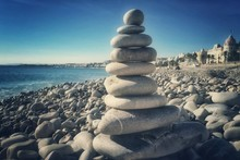 Close-up Of Stacked Stones At Beach Against Sky