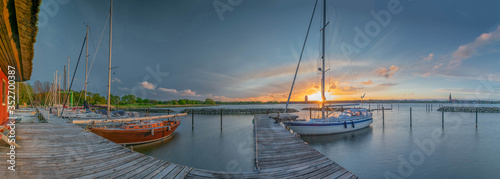 Obraz Sailing boats stowed at the pier, lit by the evening sun, sunset over small harbor with sailing boats, Schlei, Schleswig, Schleswig-Holstein, Germany - fototapety do salonu