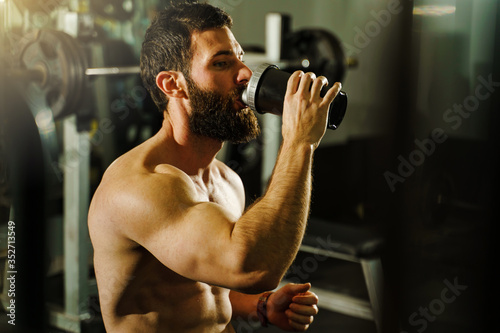 Side view portrait of young muscular caucasian man bodybuilder shirtless male si Wallpaper Mural