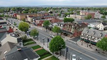 Aerial Establishing Shot Of Main Street, Small Town America, Storefronts And Colonial Homes In United States Historic Town