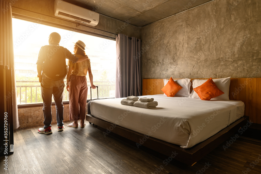 Fototapeta Portrait of young couple tourist standing nearly window, looking to beautiful view outside in hotel/resort bedroom after check-in. Conceptual of couple travel and vacation in their honeymoon period.