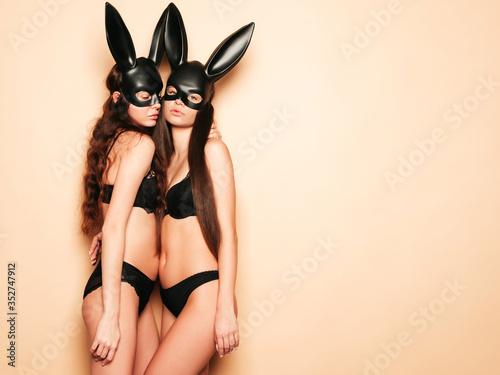 Two sexy beautiful women wearing carnival black mask of Easter bunny rabbit.Hot brunette girls posing near wall in studio. Seductive models in nice lingerie