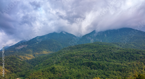 Fototapeta High mountain with rocky slopes hidden in clouds and fog. obraz na płótnie
