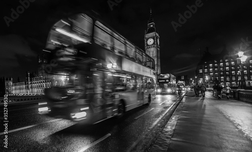 Fotografie, Tablou Blurred Motion Of Double-decker Bus On Westminster Bridge In City At Night