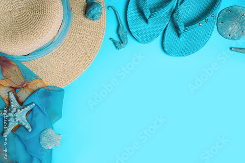 Fototapeta Summer fashion on blue background. Flip flops, seashells, and straw hat with scarf. Flat lay, top view with copy space. obraz na płótnie