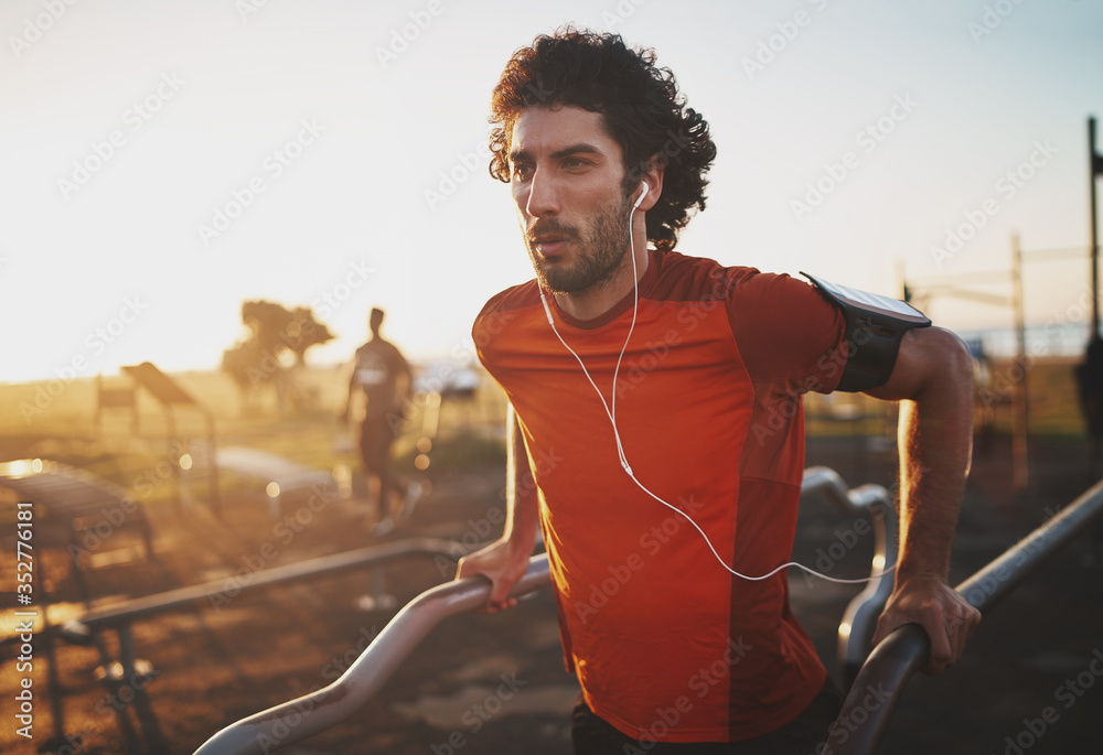 Fototapeta Portrait of an athletic young man listening to music on earphones doing exercise on parallel bars in the park - young man doing dips outdoors